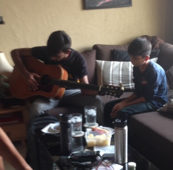 Dana teaching guitar to one of the Pakistani refugee boys